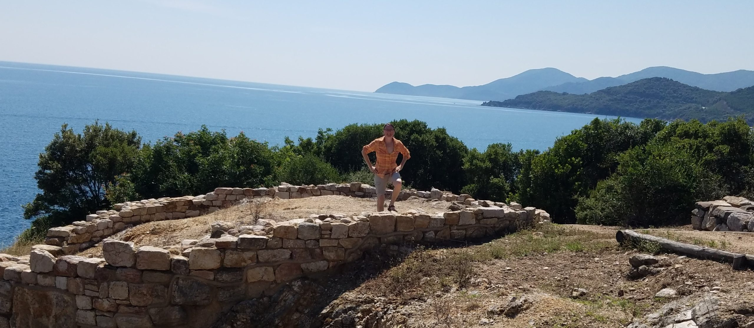 A picture of me standing in the ruins of Ancient Stagira, Greece, with mountains and the sea in the background
